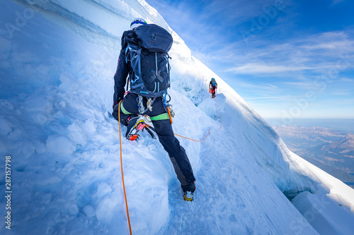 Two alpinists mountaineers climbing over ice crevasse. Fototapet