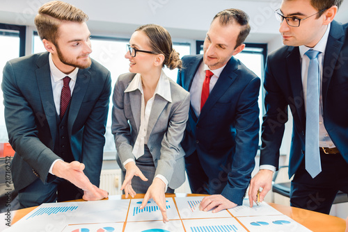 Photo Team analyzing financial data in charts on a table
