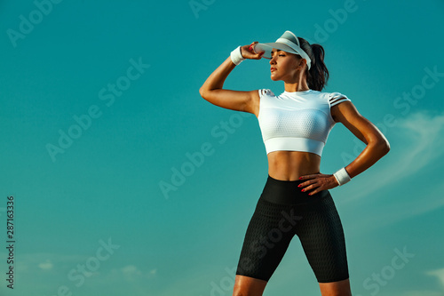 Keuken foto achterwand Ontspanning Sporty and fit young woman athlete relaxed after yoga training on the sky background. The concept of a healthy lifestyle and sport. Individual sports recreation.