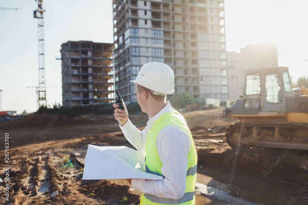Fototapety, obrazy: working engineer talking on the radio at the construction site