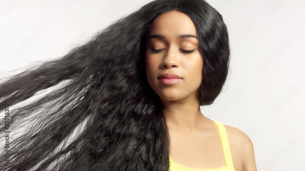 Fototapeta beauty mixed race african american model in studio portraits with long hair wig natural makeup watching aside with hair blowing