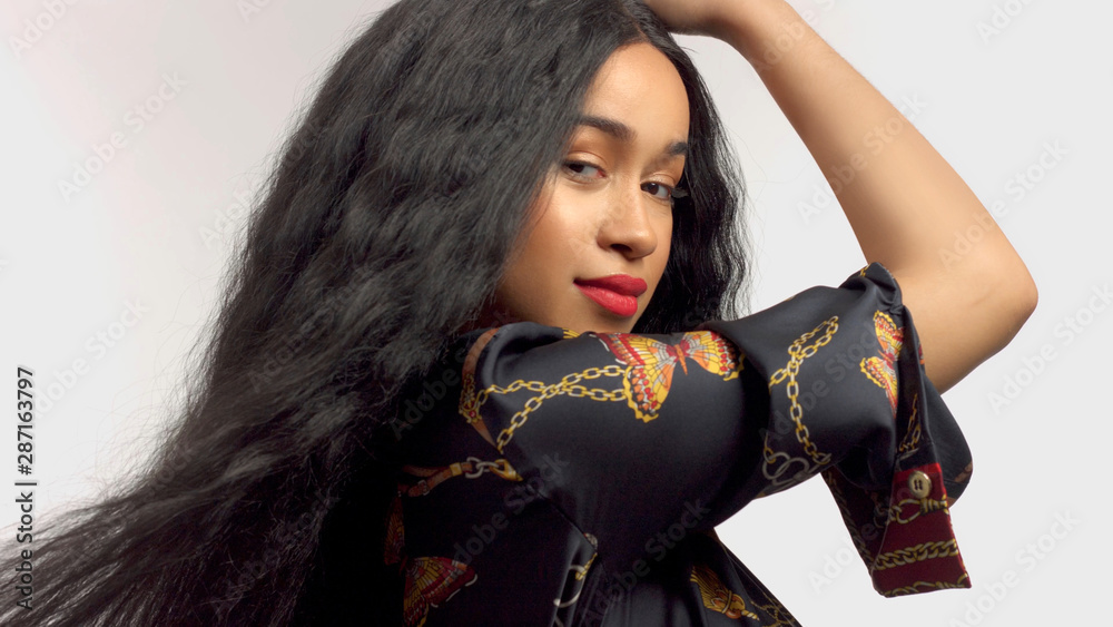 Fototapeta gorgeous mixed race model in studido shoot with long wavy wig on touches her hair