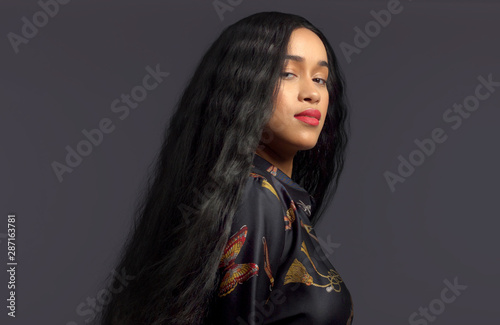 gorgeous mixed race model in studido shoot with long wavy wig on Dark background Canvas