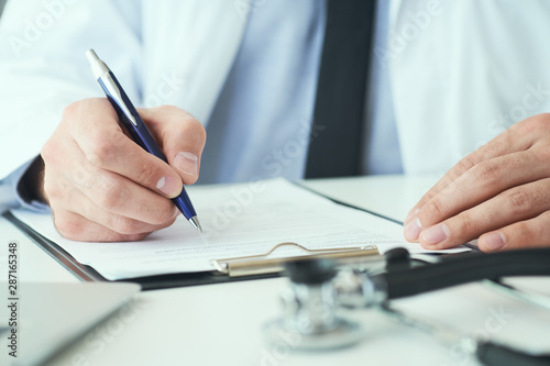 Mid section of male doctor writing write prescription to patient at worktable Fototapet