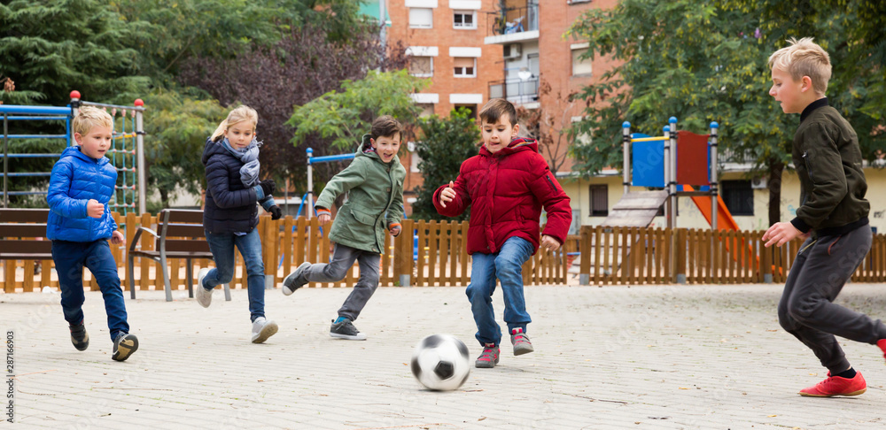 Fototapety, obrazy: Group of laughing children playing football
