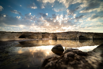 Shot of the sun rising behind the rocks at Cirica Bay at sunrise. Cirica is a beautiful nature seaside place made of cliffs, rocks and sand in the southern Sicily, Italy