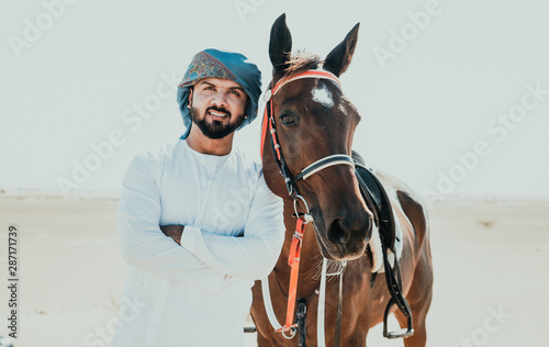 Fotografie, Obraz  Arabian man with traditional clothes riding his horse