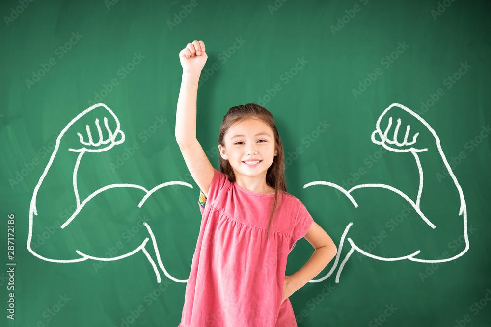 Fototapeta little girl standing against chalkboard and strong winner concept