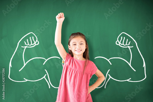 Fotografiet  little girl standing against chalkboard and strong winner concept