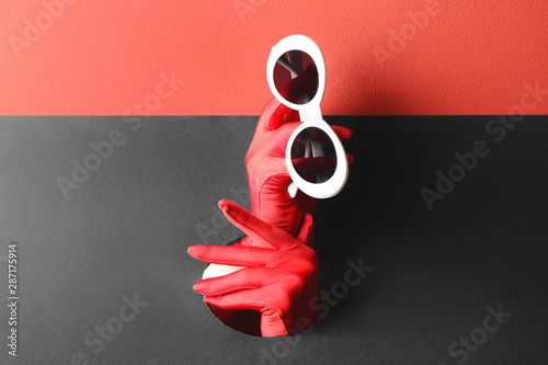 Fotomural Female hands holding stylish sunglasses through hole in paper