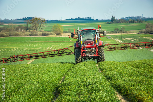 Tractor spraying the rural green field