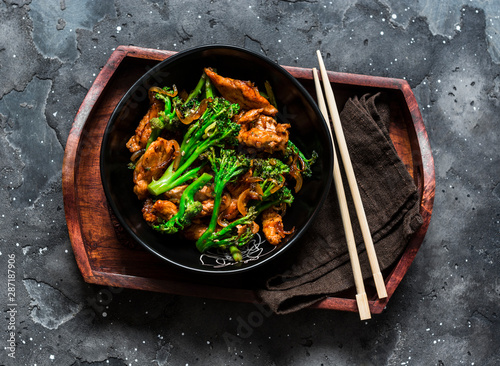 Cuadros en Lienzo Teriyaki stir fry chicken with broccoli on wooden tray on dark background, top v