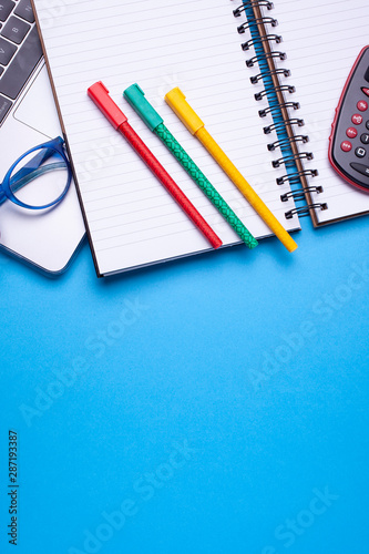 Flat lay top view mockup photo of working space with laptop, pocket calculator, pens, glasses and notebook on blue pastel background. - 287193387
