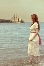 Vintage Style Woman Walking In Ocean With Tall Ship