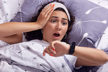 Oversleeping Concept. Young Woman Missed Ringing Alarm Clock, Be Late, Looking With Horror At Clock On Hand, Lying In Bed, Has Shocked Facial Expression, Having Blindfold On Head, Keeps Mouth Opened.