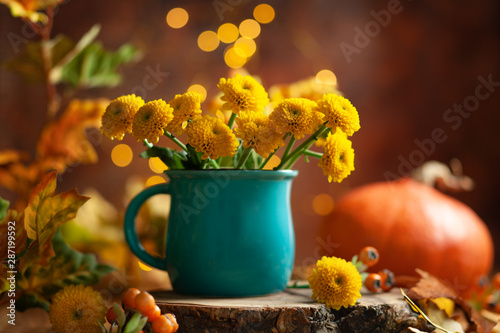 Slika na platnu Beautiful yellow flower in blue cup on wooden table at bokeh  background, front view