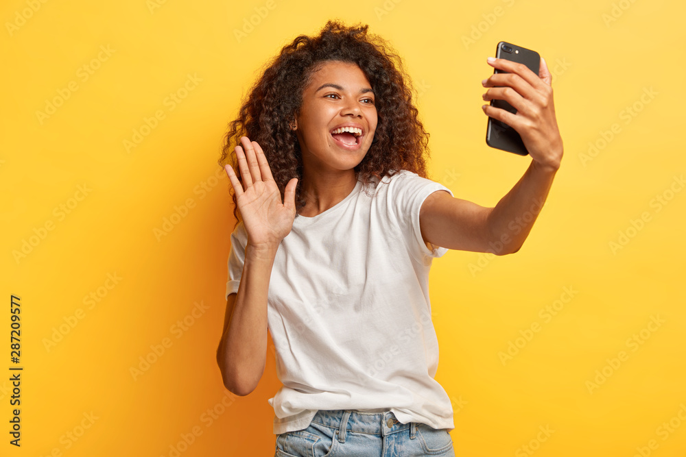 Fototapety, obrazy: Glad dark skinned happy woman with Afro hairstyle, holds modern mobile phone in front of face, waves palm in camera, makes video call, dressed in casual wear, isolated over yellow studio wall.