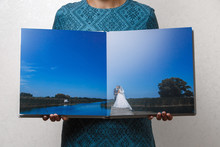 A Woman Holds Open Family Phot...