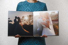 Woman Holds Open Family Photobook. The Person Looks At The Photo Book Turn.  Beige Sample  Photo Album . Wedding Photoalbum With  Fabric Cover .female Hands Holding Square Open Photo Album.