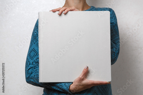 Fotografija  a woman holds a family photobook the person looks at the photo book sample  beige photo album  wedding photoalbum with  fabric cover