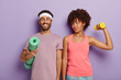 canvas print picture - Smiling pleased man poses with fitness mat, wears purple t shirt and headband, lovely sporty woman looks at husband, trains biceps with weight, stand shoulder to shoulder indoor. Aerobics and people