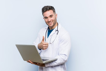 Caucasian Doctor Man Holding A Laptop Smiling And Raising Thumb Up