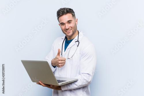 Fotografía  Caucasian doctor man holding a laptop smiling and raising thumb up