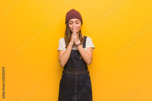 Young hipster woman praying very happy and confident Fototapete