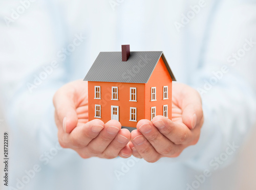 Photo sur Toile Les Textures Small orange toy house in hands