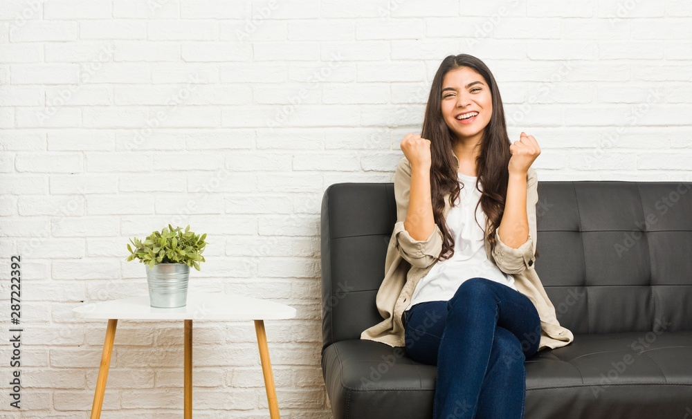 Fototapeta Young arab woman sitting on the sofa cheering carefree and excited. Victory concept.