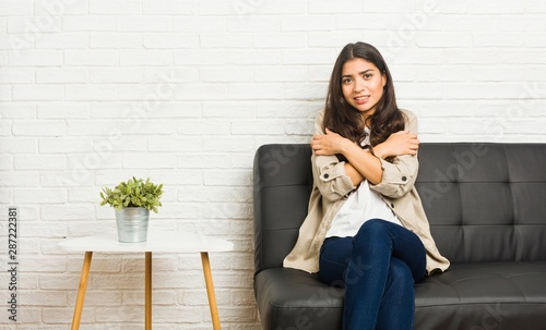 Canvas Print Young arab woman sitting on the sofa going cold due to low temperature or a sickness