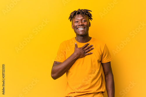 Fotografie, Obraz  Young black man wearing rastas over yellow background laughs out loudly keeping hand on chest