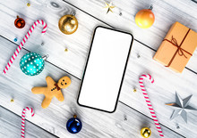 Smartphone Blank Screen Template With Christmas Stuff Around - Giftbox, Candy, Gingerbread Man, Balls, Stars And Beads