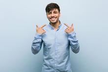 Young Hispanic Business Man Smiles, Pointing Fingers At Mouth.