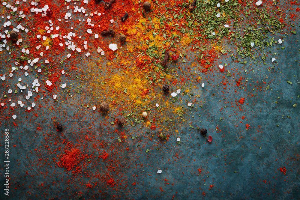 Fototapeta Different spices scattered on the table, red paprika powder, turmeric, salt, cloves, pepper