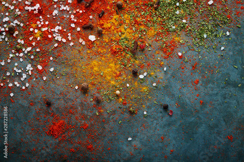 Fototapeta Different spices scattered on the table, red paprika powder, turmeric, salt, cloves, pepper obraz