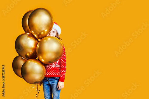 Cute children in red Santa hats and sweaters hugging and holding shopping bags a Canvas Print