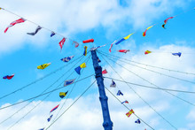Multi-colored Flags On A Rope, Against A Blue Sky. Street Decorations. Decoration Of Street Cafes.