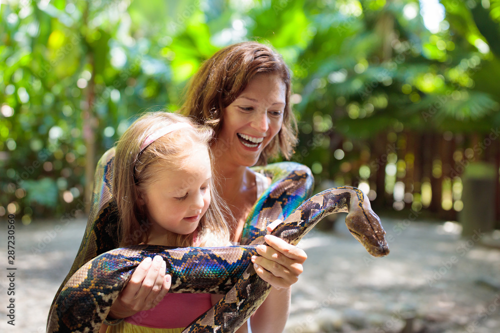 Fototapety, obrazy: Kids hold python snake at zoo. Child and reptile.