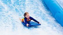 Little Girl Surfing In Beach W...