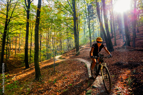 Fototapeta Cycling woman riding on bike in autumn mountains forest landscape. Woman cycling MTB flow trail track. Outdoor sport activity. obraz
