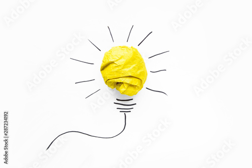 Business ideas. Composition of modern crumpled yellow paper ball and drawing of lamp bulb on white background. Creative and startup concepts.