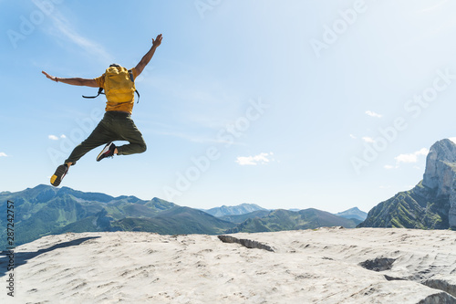 Obraz na plátně  Young Man Jumping on Top of a Mountain Wearing Yellow Backpack.