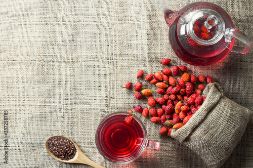 Photo  Dried rose hip glass cup of herbal tea medicinal plants with rosehip fruits in burlap sack and glass teapot on sackcloth