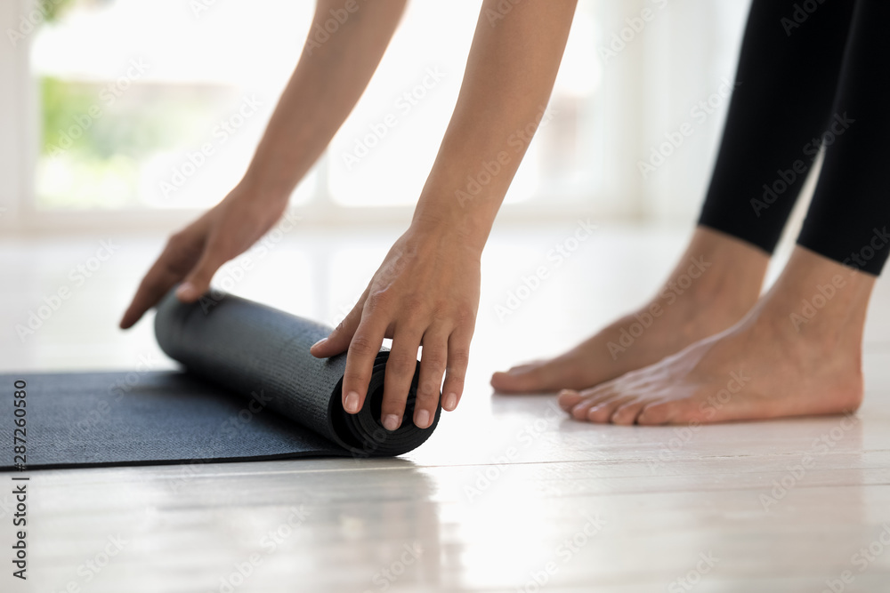 Fototapety, obrazy: Woman practicing yoga, rolling black mat side view close up