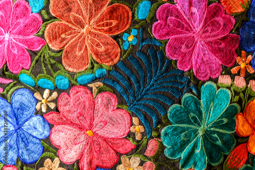 Background of hand-embroidered flowers on a fabric with colored threads.
