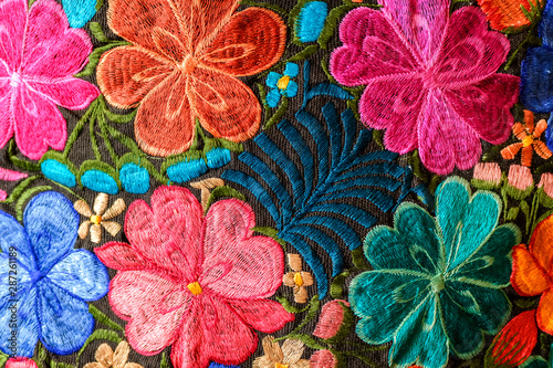 Background of hand-embroidered flowers on a fabric with colored threads. - 287261189
