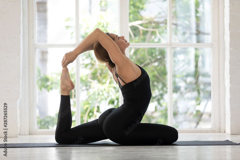 Fototapety, obrazy: Young woman practicing yoga, King Pigeon pose, Rajakapotasana exercise