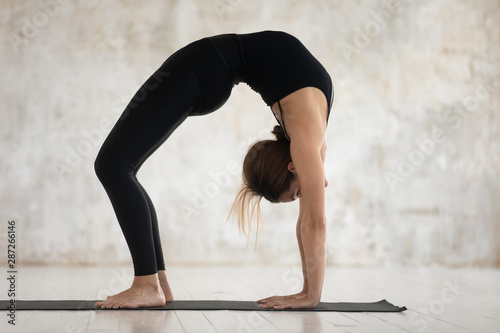 Photo  Young woman practicing yoga, Bridge exercise, Urdhva Dhanurasana