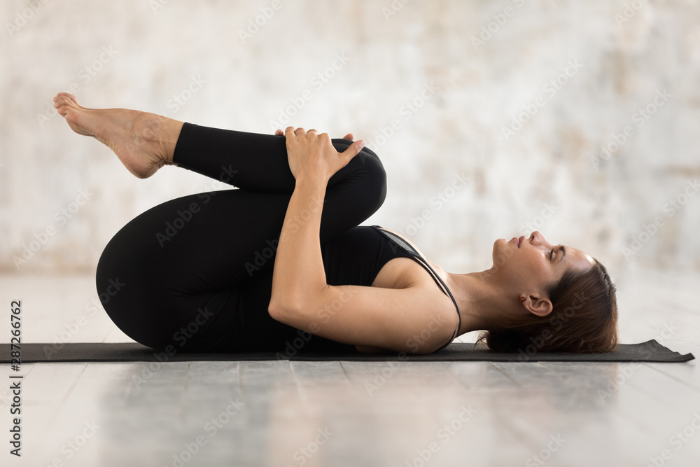 Fototapety, obrazy: Beautiful woman practicing yoga, Knees to Chest pose, Apanasana exercise